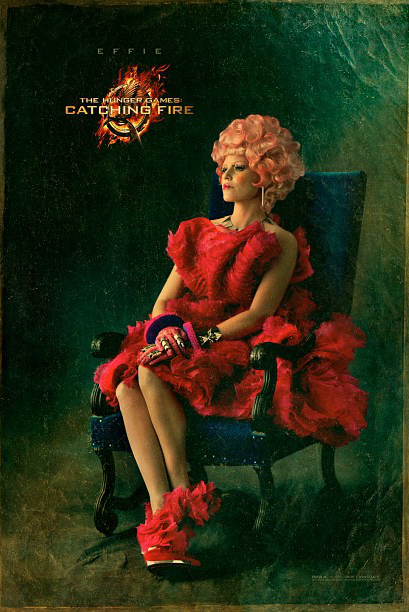 effie catching fire poster1 Lionsgate Reveals First Look At Effie Trinket And Ceaser Flickerman In Catching Fire